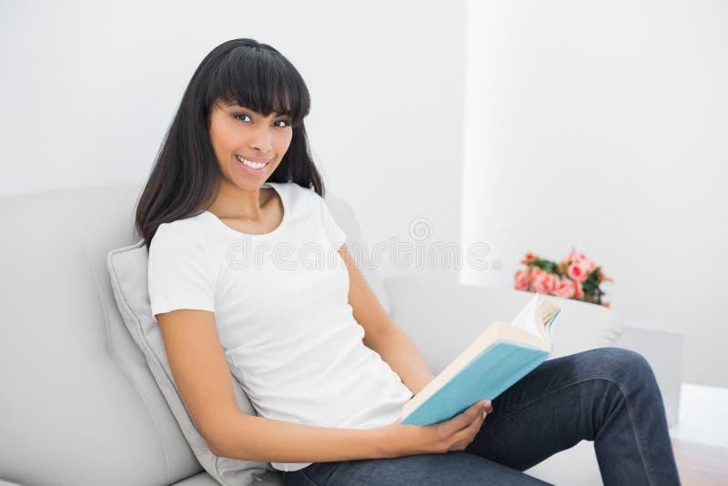 Bella donna calma che tiene un libro mentre sedendosi sullo strato fotografia stock libera da diritti