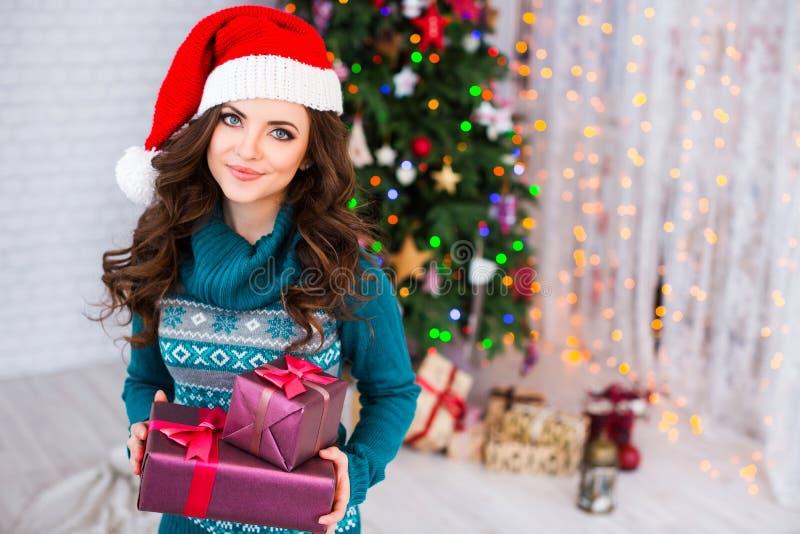 Bella donna in cappelli di Santa che tengono i contenitori di regalo sul fondo di Natale fotografia stock