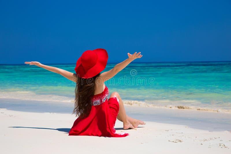 Bella donna in cappello che gode e che si rilassa sulla spiaggia con bianco immagini stock libere da diritti