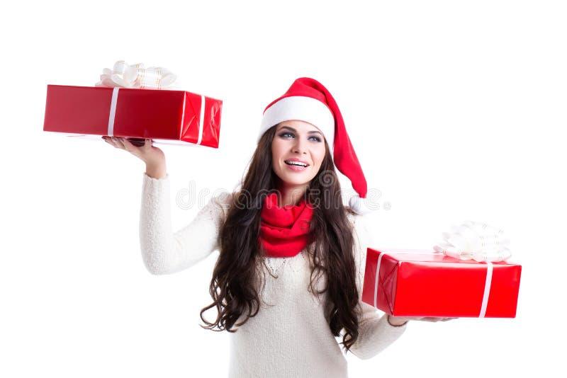 Bella donna in cappello di Santa che tiene due regali immagine stock