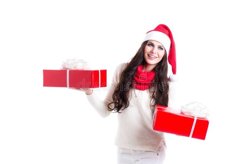Bella donna in cappello di Santa che tiene due regali Concetto delle vendite del nuovo anno Indennità del nuovo anno fotografie stock libere da diritti