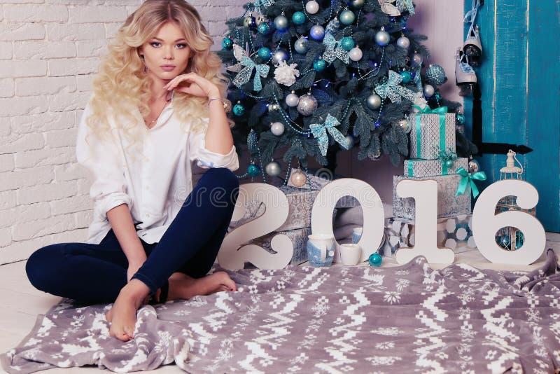 Bella donna a casa accogliente, con i presente e la decorazione del nuovo anno immagini stock libere da diritti