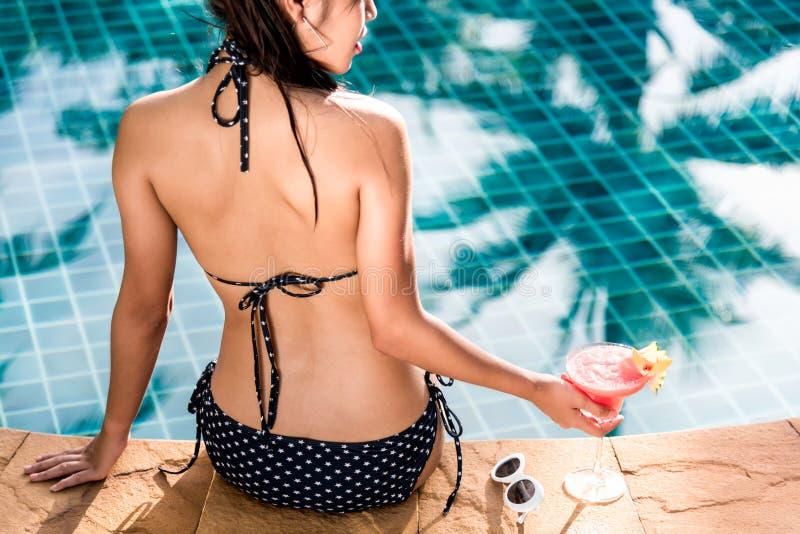 Bella donna castana in bikini nero che gode rilassandosi sitti fotografie stock libere da diritti
