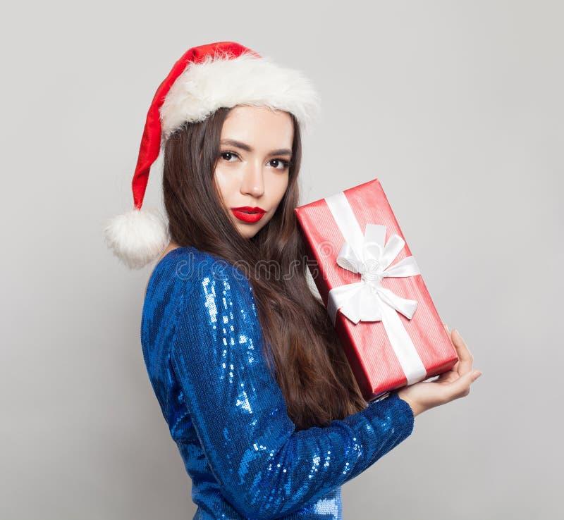 Bella donna castana in cappello di Santa che tiene il regalo di Natale immagini stock