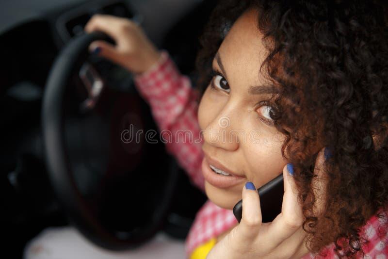Bella donna castana che conduce automobile blu, parlante mentre guidando Sguardo esterno e sorridere e parlare sul telefono fotografie stock libere da diritti