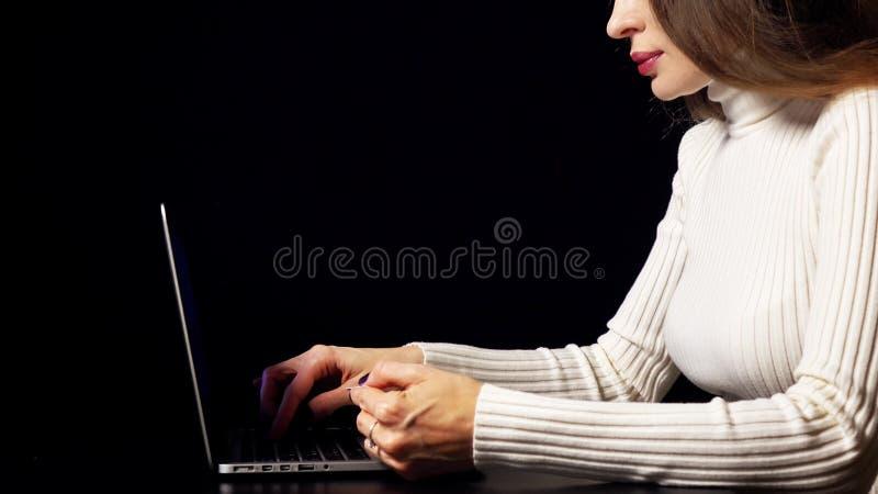 Bella donna castana che effettua pagamento online con la sua carta di credito facendo uso del computer portatile Fondo nero, colo immagine stock