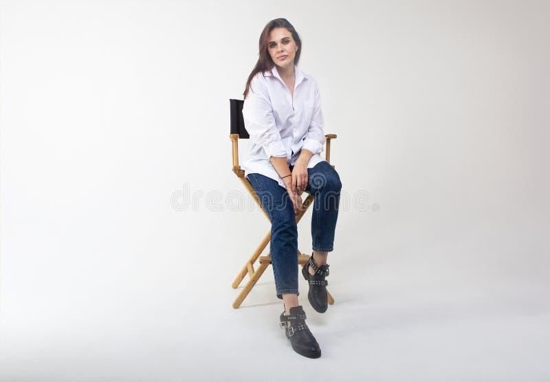 Bella donna castana che posa allo studio in camicia bianca immagini stock libere da diritti