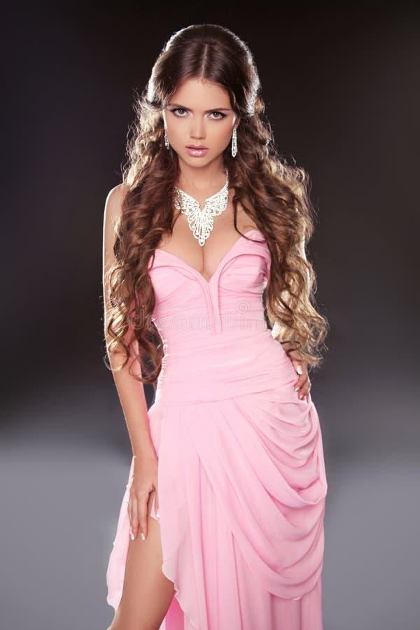Bella donna castana che posa in vestito splendido rosa isolato fotografie stock
