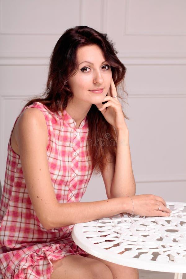 Bella donna castana che si siede vicino ad una tavola fotografia stock