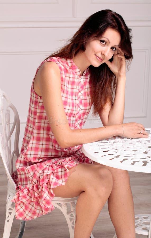 Bella donna castana che si siede vicino ad una tavola immagine stock