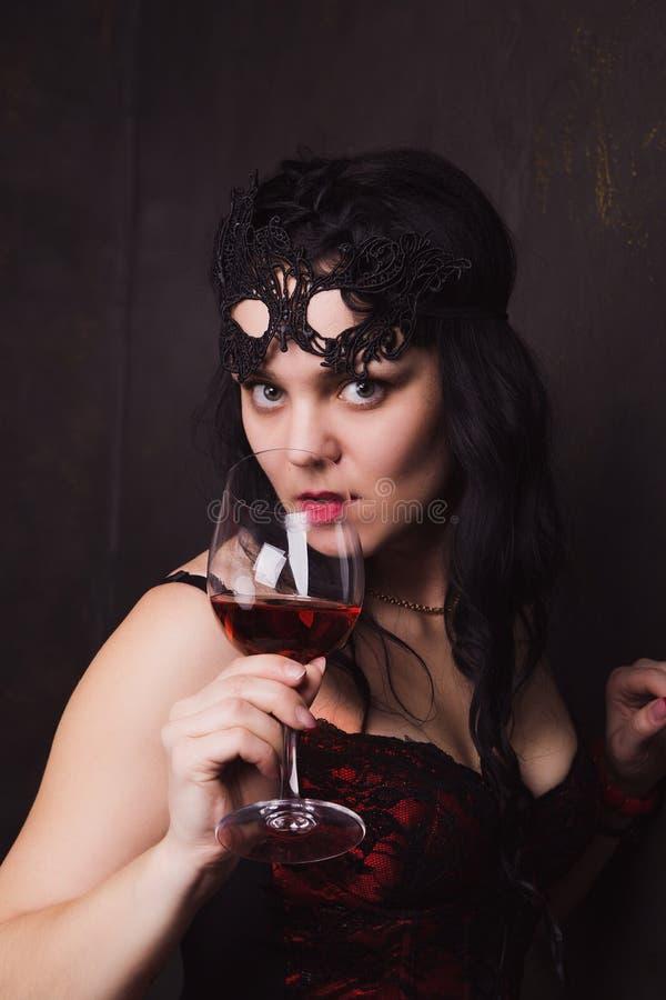 Bella donna castana che tiene un vetro di vino rosso immagini stock