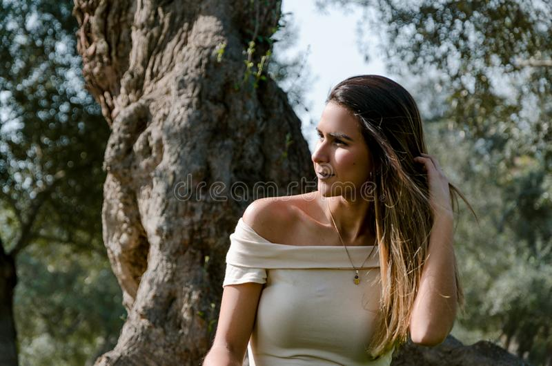 Bella donna castana che tocca i suoi capelli lunghi Si siede in un parco su erba verde fotografia stock