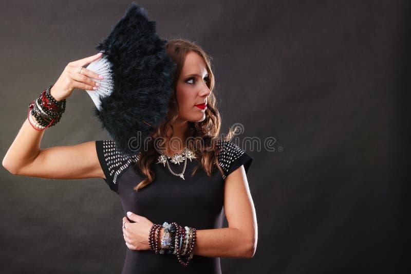 Bella donna castana con il fan nero a disposizione immagine stock