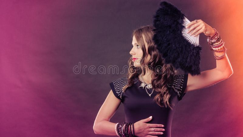 Bella donna castana con il fan nero a disposizione fotografie stock