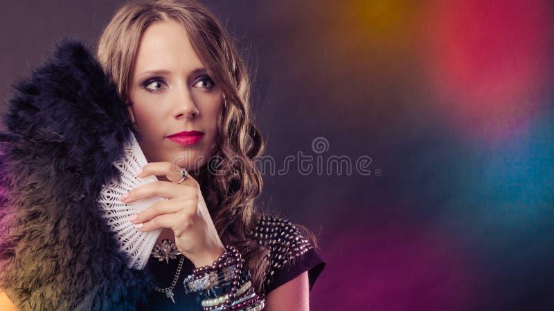 Bella donna castana con il fan nero a disposizione fotografia stock libera da diritti