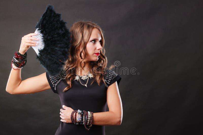 Bella donna castana con il fan nero a disposizione fotografia stock