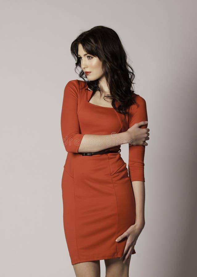 Bella donna castana con le labbra rosse ed il vestito sexy rosso che guardano al lato immagine stock libera da diritti