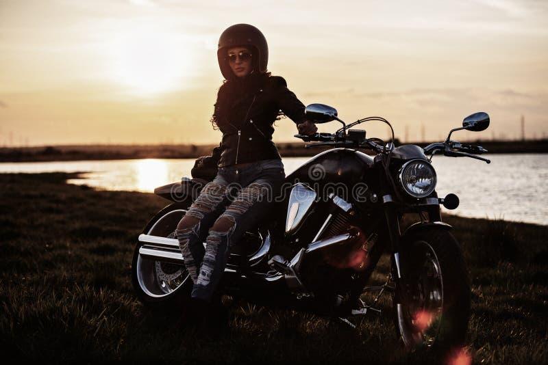 Bella donna castana con un motociclo classico c fotografia stock