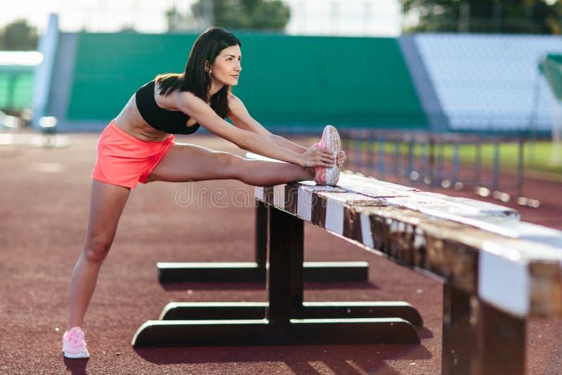 Bella donna castana del corridore che fa allungamento pendendo la sua gamba sulla barriera per eseguire allungamento prima dell'a fotografia stock libera da diritti