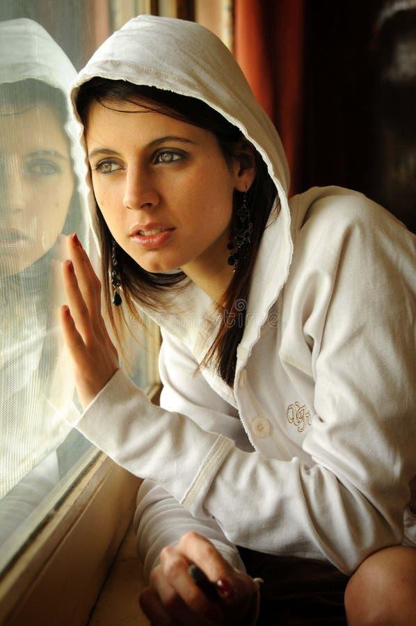 Bella donna castana nuda accanto alla finestra immagini stock