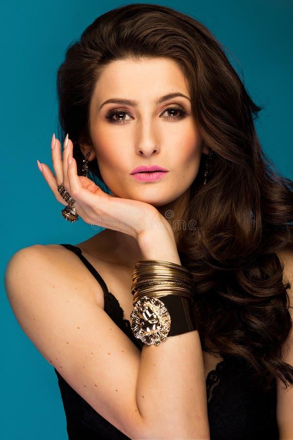 Bella donna castana sensuale che posa in gioielli neri dell'oro e del vestito Ragazza con capelli ricci lunghi fotografie stock