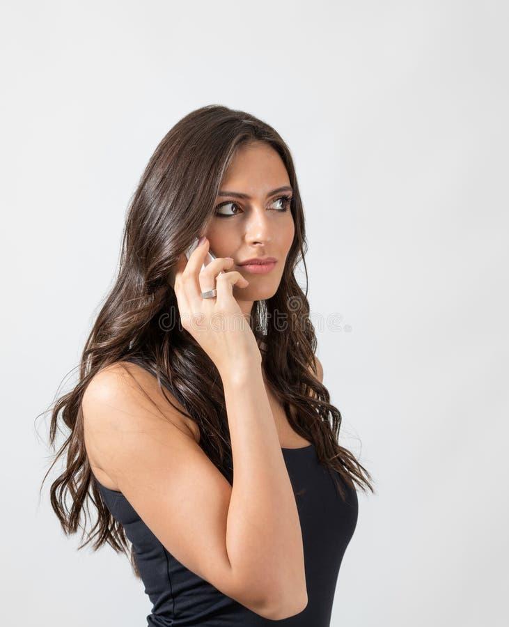 Bella donna castana sensuale con capelli lunghi che parla sul distogliere lo sguardo dello smartphone fotografia stock