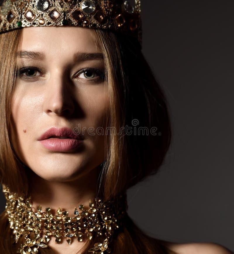 Bella donna castana sexy di bellezza con la corona ed i gioielli lunghi dell'oro di usura dei capelli su buio fotografia stock