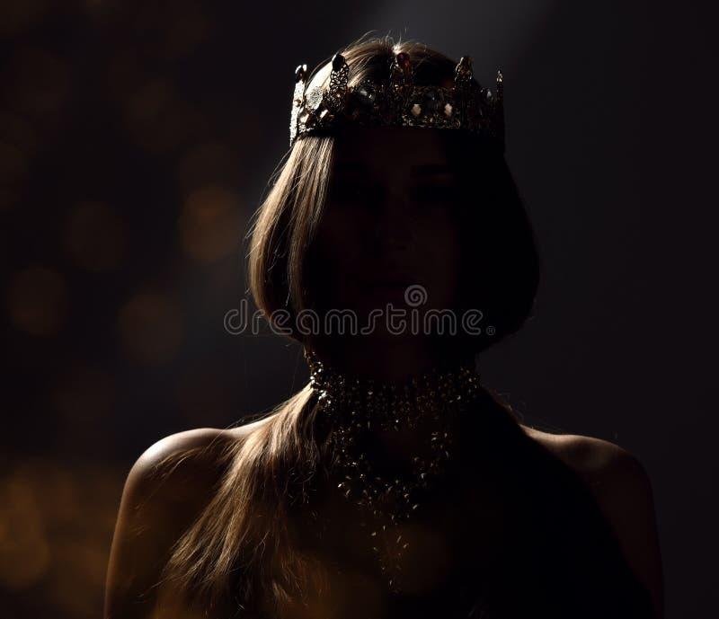 Bella donna castana sexy di bellezza con la corona lunga dell'oro di usura dei capelli su fondo scuro fotografia stock