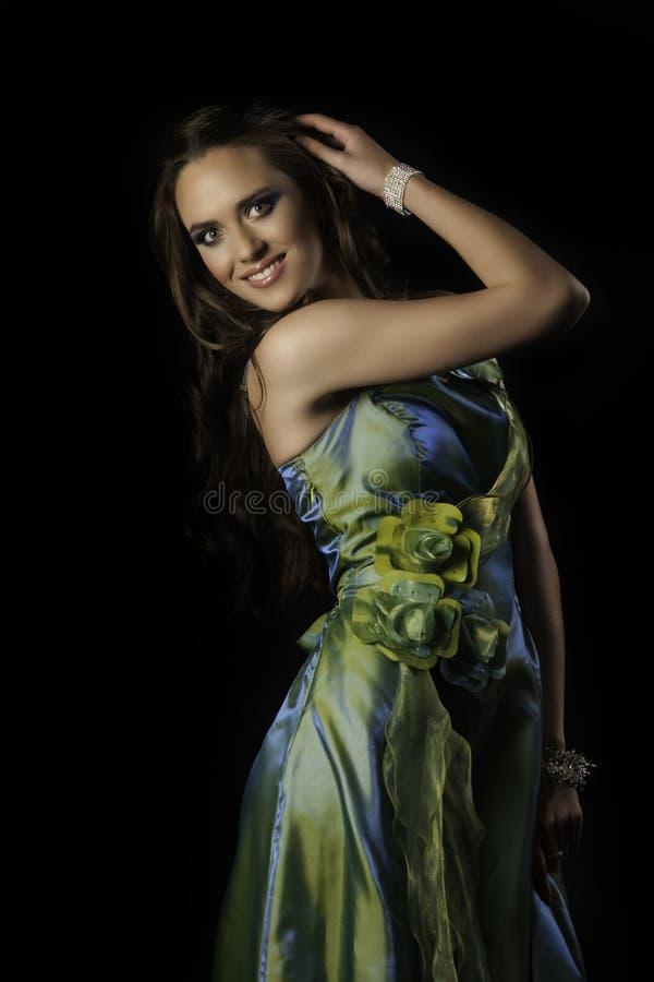 Bella donna castana smiliing nell'usura verde di sera di alte mode fotografia stock