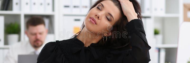 Bella donna castana sorridente in ufficio che riordina capelli fotografia stock