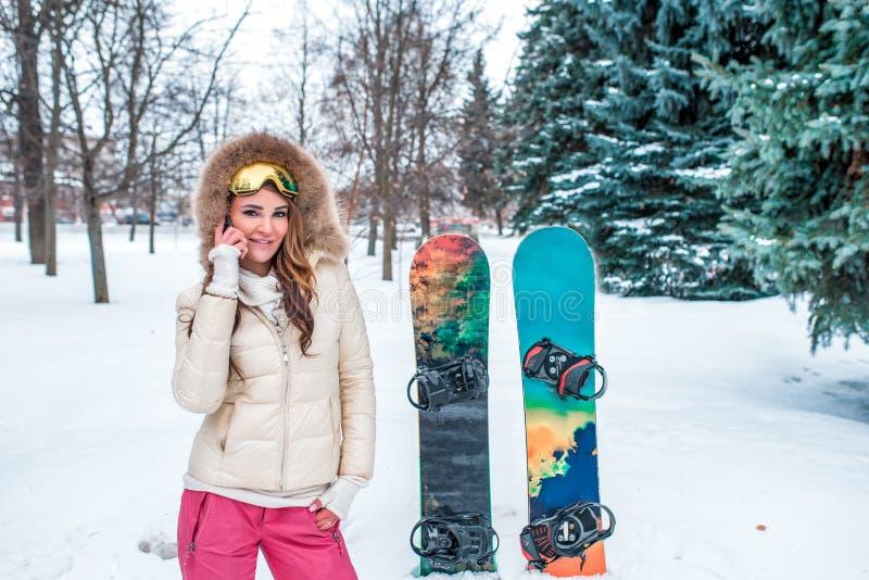 Bella donna castana su fondo degli alberi di Natale nevosi verdi, bordi dello snowboard Le chiamate telefonano Felicità di emozio fotografie stock