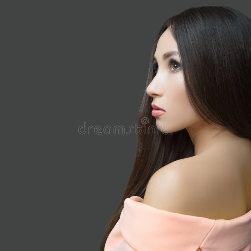 Bella donna castana tenera in un vestito rosa Capelli diritti lunghi Fondo scuro immagine stock