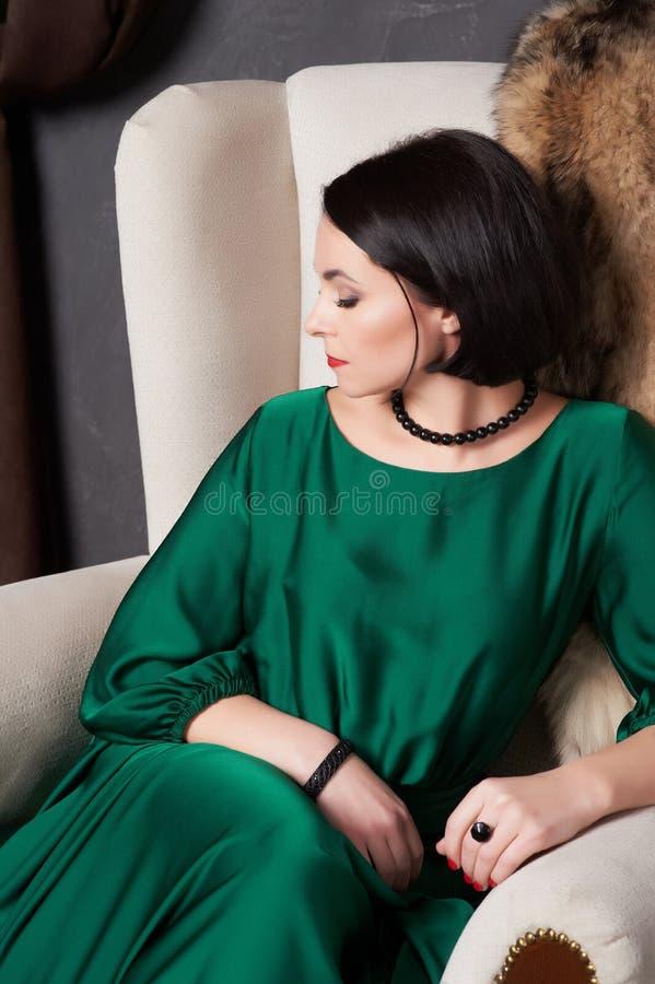 Bella donna castana in un vestito verde di seta che posa seduta in una sedia d'annata Stile della Boemia fotografie stock libere da diritti