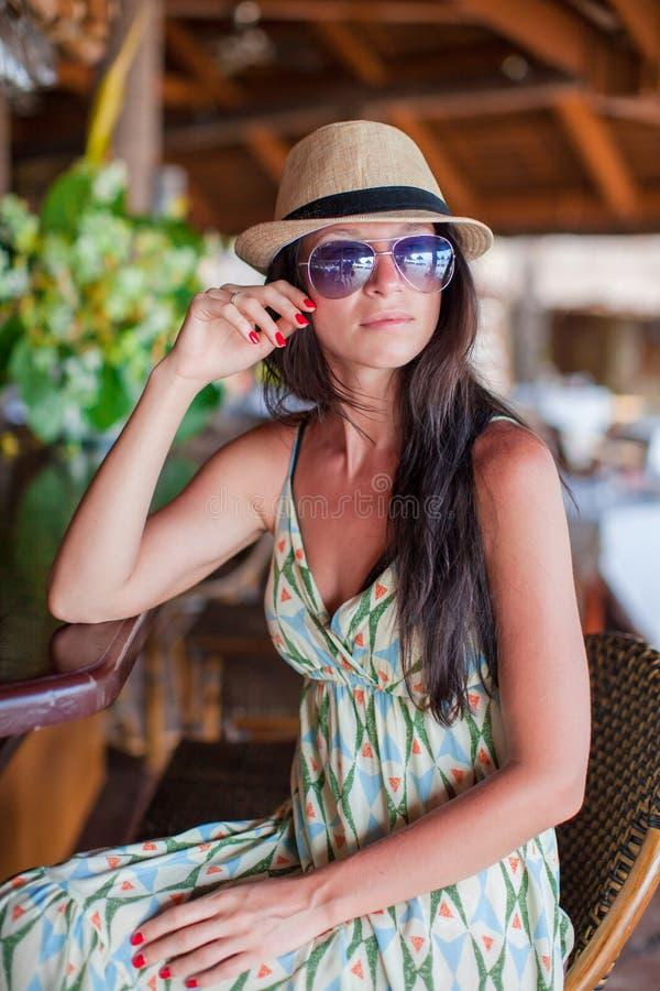 Bella donna castana in vestito lungo e cappello che si rilassano nel ristorante della spiaggia fotografia stock