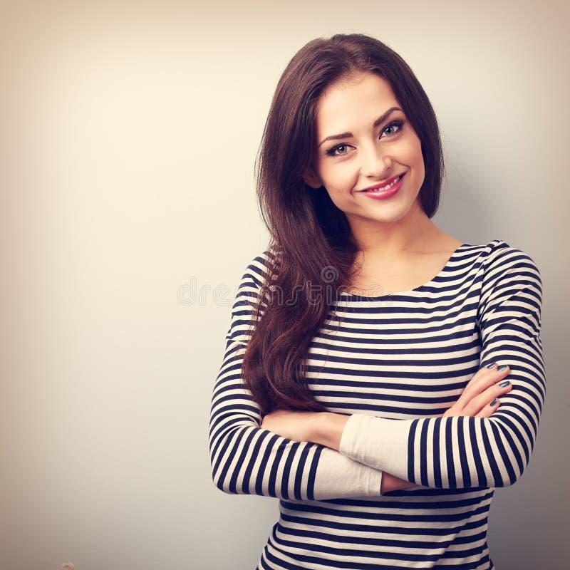 Bella donna casuale sicura con le mani piegate che sembrano felici fotografia stock