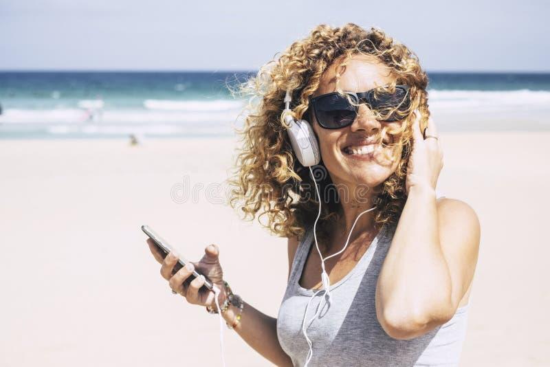 Bella donna caucasica attraente allegra di medio evo che sorride alla spiaggia nel posto tropicale mentre ascolta la musica con l fotografia stock libera da diritti