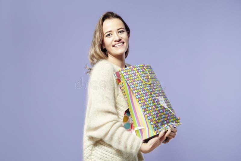Bella donna caucasica bionda soddisfatta dei sacchi di carta attuali in mani Maglione caldo d'uso, emozioni felici fotografia stock