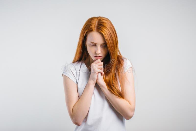 Bella donna caucasica della testarossa che prega a casa immagine stock libera da diritti