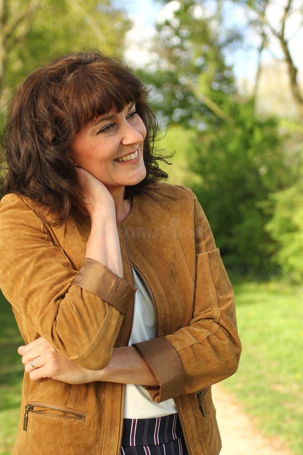 Bella donna caucasica matura felice fuori nel parco fotografie stock