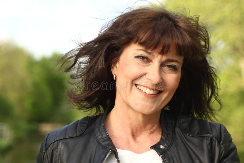 Bella donna caucasica matura felice fuori nel parco immagine stock