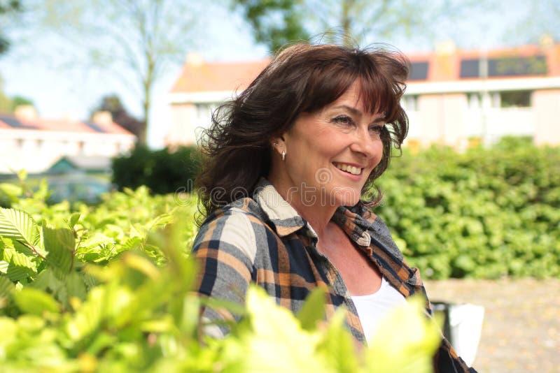 Bella donna caucasica matura felice fuori nel parco immagini stock libere da diritti