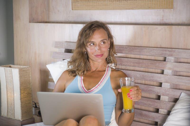 Bella donna caucasica 30s che si siede sul letto alla notte in camera da letto domestica facendo uso di Internet al computer port fotografie stock