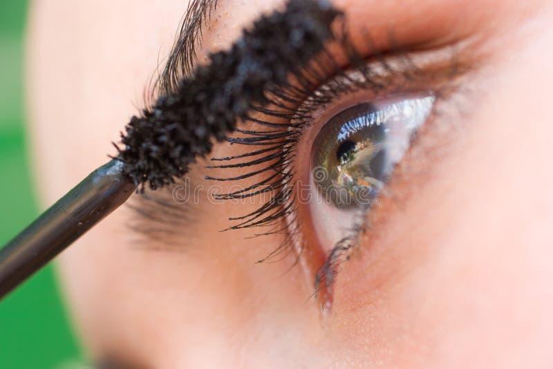 Bella donna che applica mascara sull'occhio con la spazzola fotografia stock