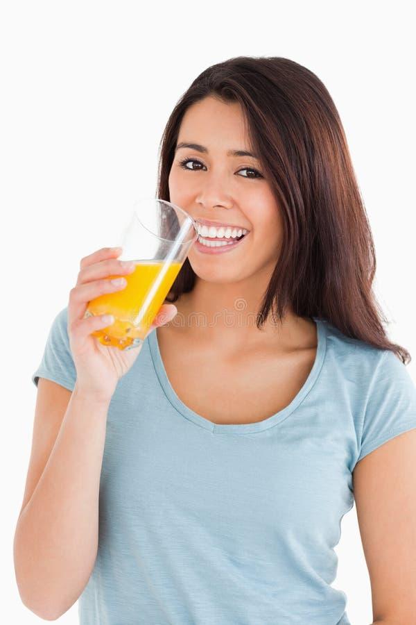 Bella donna che beve un vetro del succo di arancia fotografie stock libere da diritti