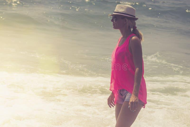 Bella donna che cammina sulla spiaggia Donna rilassata che respira aria fresca, donna sensuale emozionale vicino al mare, godente immagine stock