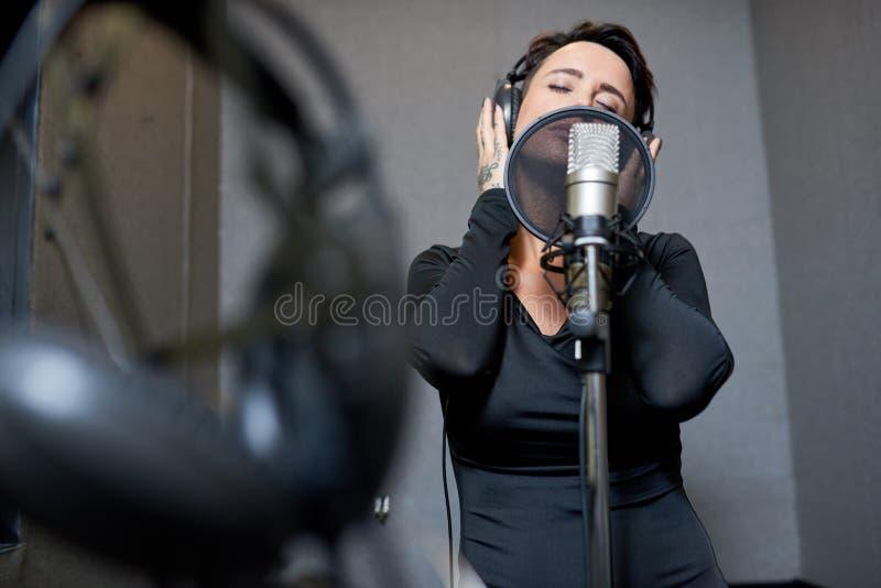 Bella donna che canta nello studio immagini stock libere da diritti