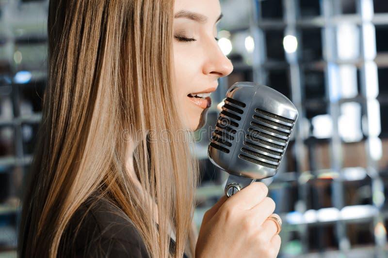 Bella donna che canta sulla fase accanto al microfono fotografia stock