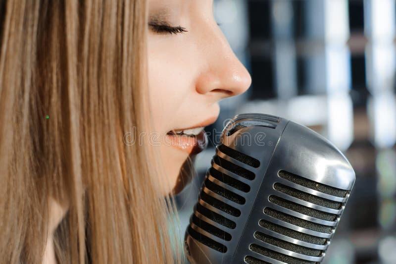 Bella donna che canta sulla fase accanto al microfono fotografia stock libera da diritti
