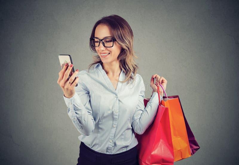 Bella donna che compera online controllando i prezzi sul telefono cellulare immagini stock