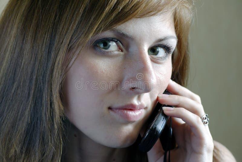 Bella donna che comunica dal mobile immagine stock